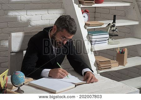 Professor In Glasses With Serious Face Writes In Book
