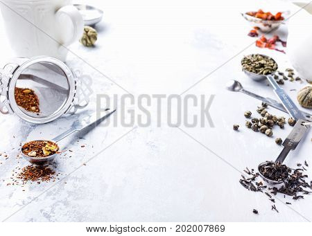 Background with different types of tea leaves, black, green, rooibos and strawberry with tea making facilities. Healthy drink concept. Copy space.