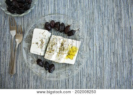 White goat's cheese with sun dried olives and olive oil.