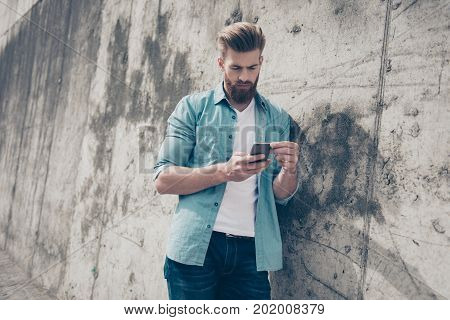 Young Serious Man In Casual Clothes Leaning On The Concrete Wall And Using Smartphone For Sending Sm