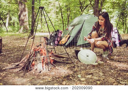Young attractive brunette lady is cooking canned goods and veggies in a cattle at the camp in a forest smiling enjoying near the fire place with the setted tripod