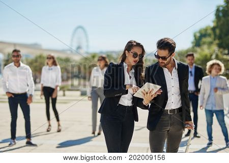 Woman On Business Trip With Coworkers Pointing At Tablet