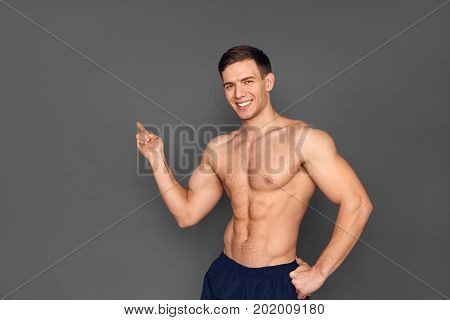 Young shirtless sportsman looking at camera and pointing away on gray background.
