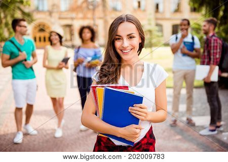 Focused shot of cheerful smart brunette caucasian girl is holding note book smiling standing near college building her friends are behind they passed tests so cheerful and carefree!