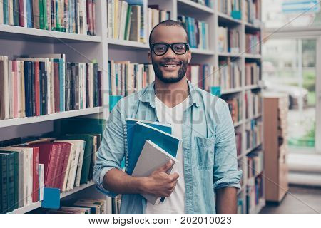 Young cheerful attractive successful african nerdy student is standing with book in the school library archive room many tomes of ancient textbooks on shelves on the background behind