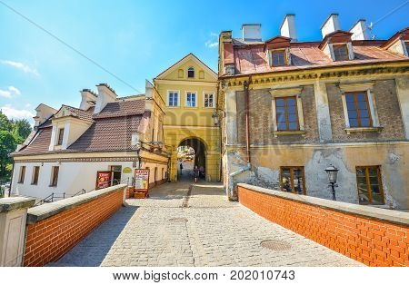 Lublin, Poland -  August 10, 2017: Beautiful bridge and old Brama Grodzka Gate to Old town of Lublin. View from the bridge of Zamkowa street, Poland. Lublin old town city center, Poland.