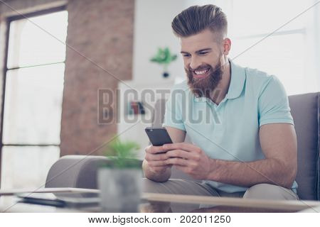 Portrait Of Happy Smiling Stylish Red Bearded Guy, Sitting On Sofa And Typing Sms On Smartphone, Wit