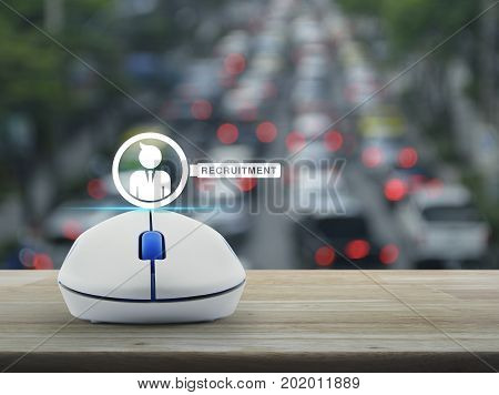 Businessman and magnifying glass icon with wireless computer mouse on wooden table over blur of rush hour with cars and road Recruitment on line concept