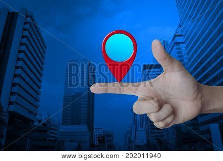Map pin location button on finger over modern office city tower Map pointer navigation concept
