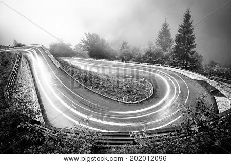 Monochrome hairpin curve mountain road with car lights in night. Dangerous driving conditions with fog, slippery surfacea and low visibility. Alps, Slovenia.