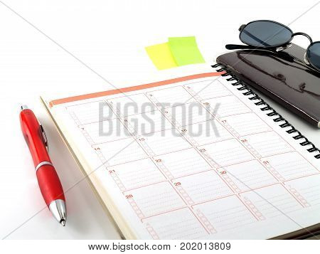 notebook, red pen, passport and sunglasses on white background, diary calendar for vacation travel planner