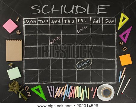 Grid timetable schedule with stationery on black chalkboard background