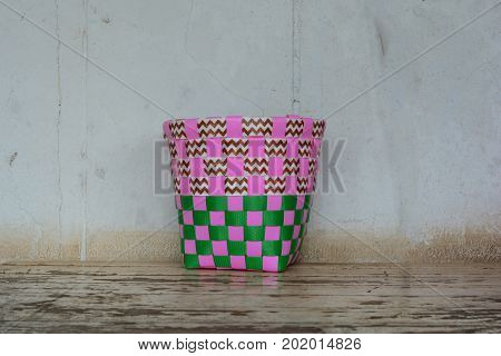 a pink and green plastic basketry on old wooden table