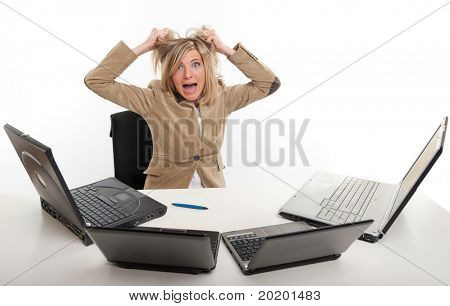 Panicked young woman in front of four laptops