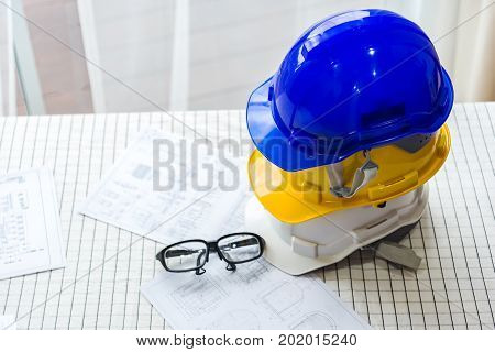 white yellow and blue hard safety helmet hat for safety project of workman as engineer or worker on concrete