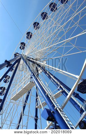 Blue and white ferris wheel seen from below against a cloudless blue sky, vertical aspect