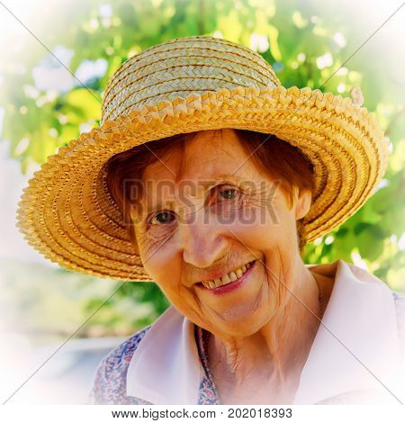 Portrait of a smiling woman in a straw hat. Age eighty years.