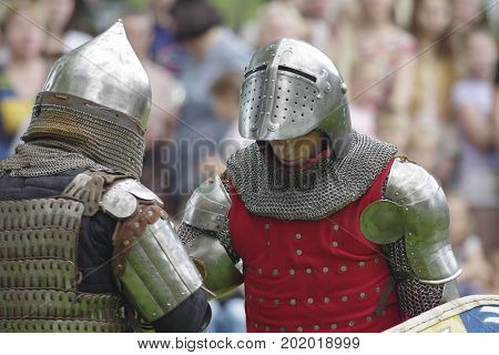 Two medieval knight in steel helmet on blurred background