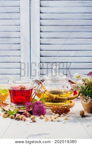Herbal tea with herbs and flowers in a glass tea pot. Copy space