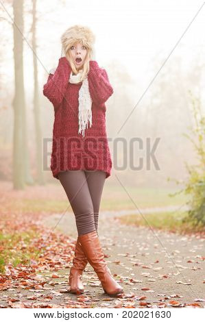 Pretty amazed surprised fashionable woman in fall forest park. Gorgeous young girl in fur winter hat maroon sweater pullover and brown boots. Autumn fashion. Full length.