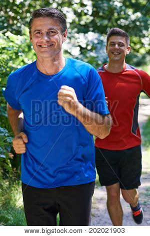 Two Men Running Along Countryside Path Together
