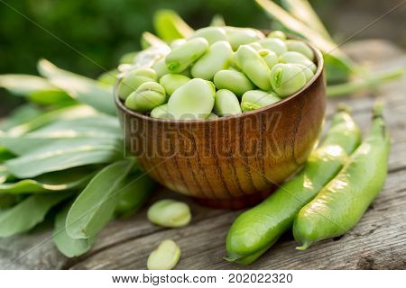 Fresh broad beans in a bowl on an outdoor wooden picnic table.