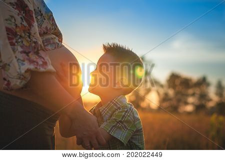 Cute boy kissing and listening his mothers pregnant mehandi pattern ornament belly on sunset nature landscape