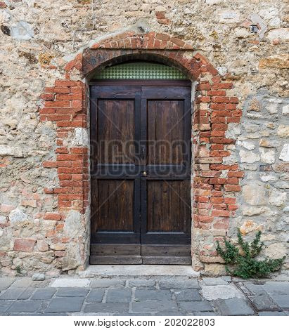 Old wooden door set in stone wall with red bricks around it.