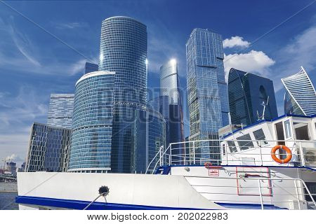 View on white touristic boat motor ship on Moscow river and Moscow City business center skyscrapers office buildings luxury apartments. Moscow river sightseeing boat tours Modern european architecture