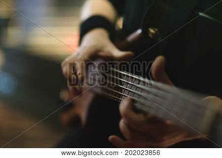 Man bass guitarist playing electrical guitar on concert stage