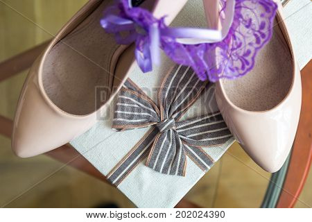 Wedding details. Purple Garter on Bride's Slippers. Box with a gift.