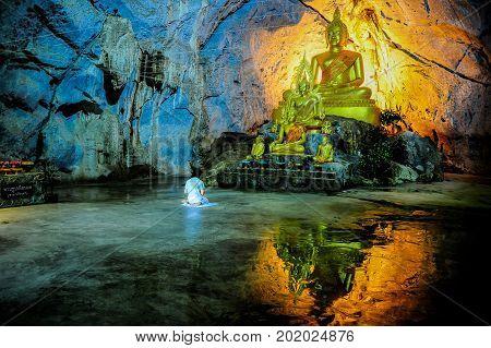Saraburi Thailand - June 2 2012 : Woman in white dress meditating in fron of Buddha image in the cave in Saraburi Thailand