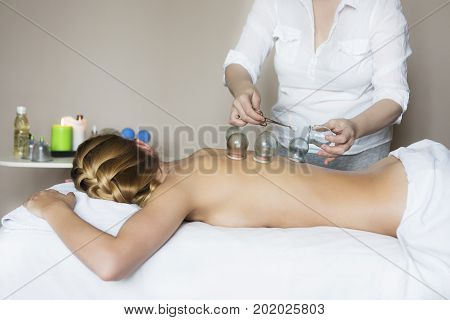 Young woman getting treatment at medical clinic. Fire cupping cups on back of female patient in Acupuncture therapy