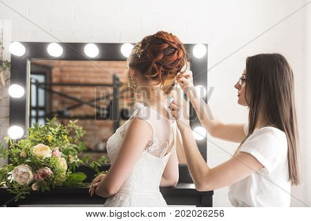 Young pretty bride and stylist in studio before wedding ceremony