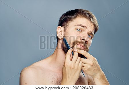 Young guy with a beard on a gray background combing.