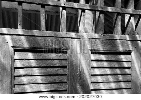 Closeup on rustic old wooden window detail with ventilation void above in black and white.