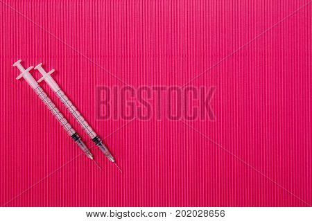 Medical syringe. Syringe for insulin on a red background