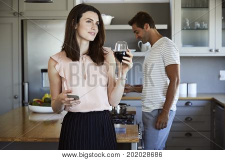 Beautiful woman in kitchen with wine and phone