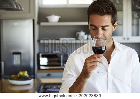 Young Guy trying wine in kitchen smiling