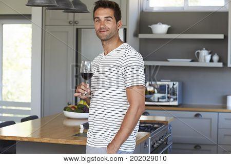 Portrait of handsome man with wine in kitchen