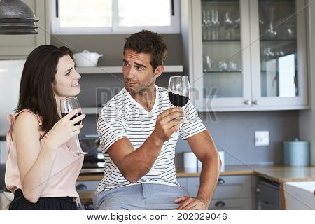 Young Couple tasting wine together in kitchen