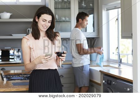 Smiling woman with wine in kitchen texting