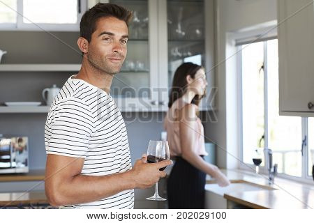 Smiling guy with wine in kitchen looking away