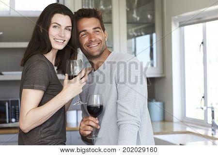 Beautiful kitchen couple smiling over wine portrait