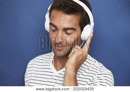 Dude lost in music on his headphones in studio