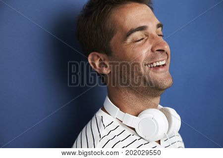 Laughing dude with headphones in blue studio