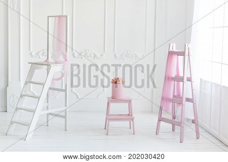Simple white interior, pink ladder decor and flowers in the box
