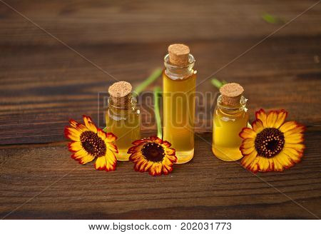 Essential Oil On Table In Beautiful Bottle With Flowers