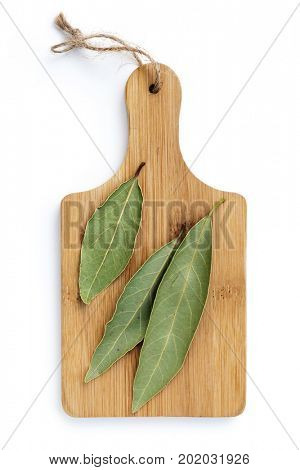 Dried bay leaves on wooden chopping board isolated on white, top view.