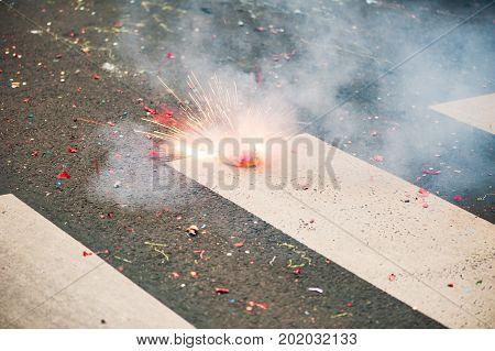 Firecracker exploding on the asphalt of a street, Paris, France